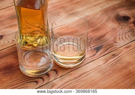 Two Glasses Of Whiskey Stand Next To The Decanter On A Wooden Table.