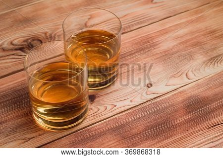 Two Glasses With Whiskey Stand On A Wooden Table.
