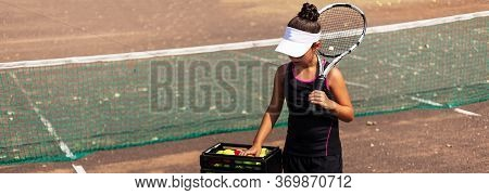 Panoramic Portrait Of Teenage Girl Playing Tennis On Tennis Court. Holding Racquet On Shoulder, Taki