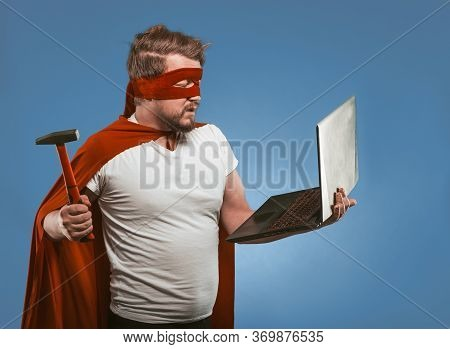 Super Hero Man Going To Smash Or Repair Laptop Computer With Hammer. Side View Of Masked Man In Red