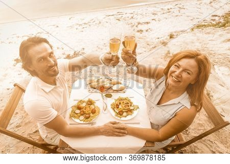 Happy Couple Raises Celebratory Toast Outdoors. High Angle View Of Smiling Mature Man And Woman Clin
