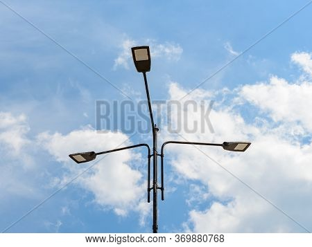 Three Led Street Lights On A Pole Against Blue Sky With Light Clouds. Modern Energy-saving Technolog