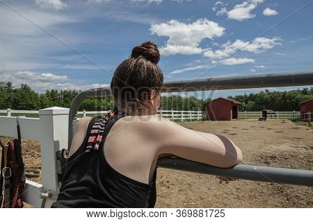 Girl Looking Into Paddock At Her Horse.