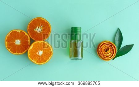 Bottle With Aromatic Tangerine Oil, Cut Tangerines And Peel On A Green Background. Essential Oils In