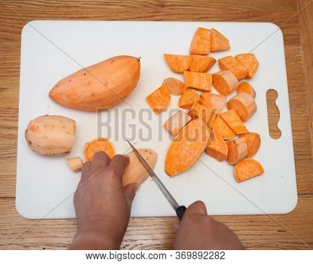Sweet Potatoes Being Chopped On A Chopping Board