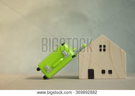 Miniature Green Suitcase With Miniature Wooden House. Concept Of Vacation Rentals, Renting Private H