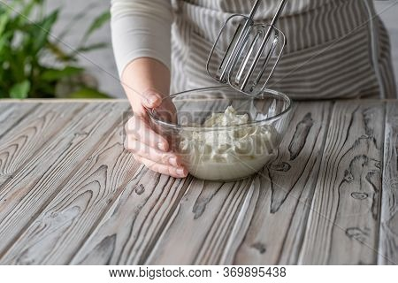 Woman Whipping Cream Using Electric Hand Mixer On The Gray Rustic Wooden Table