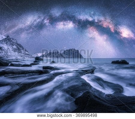 Milky Way Over The Snow Covered Mountains And Rocky Beach In Winter At Night In Lofoten Islands, Nor