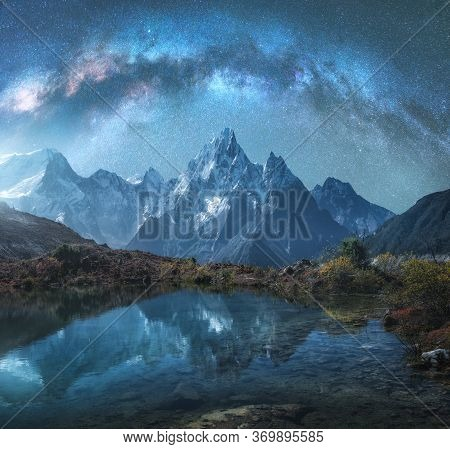 Milky Way Over Snowy Mountains And Lake At Night. Landscape With Snow Covered High Rocks And Starry