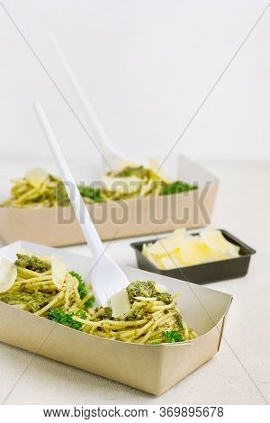 Pasta With Pesto Sauce Decorated With Parmesan And Curly Parsley In A Take-away Box From The Restaur