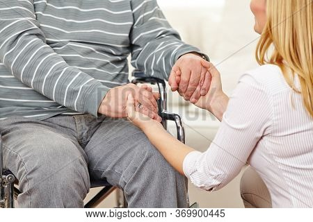 Woman holds the two hands of a disabled senior citizen in a wheelchair