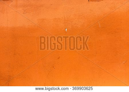 Bright Orange Wall With Antique Stucco. Plastered Wall Of An Antique Building. Abstract Texture Or B