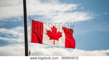 Canadian Flag Waving At Half-mast Against A Blue Sky