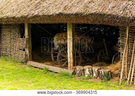 Scenic Landscape View Of Ancient Traditional Ukrainian Barn With A Straw Roof And Wicker Walls. Old