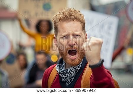 Angry man raising voice and leading a group of demonstrators on road. Furious man at climate change and save planet earth strike. Portrait of activist shouting in rally protest on global strike.