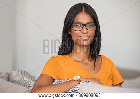 Portrait of middle eastern woman wearing eyeglasses and relaxing on couch at home. Successful indian girl with spectacles thinking and looking at camera. Satisfied young woman at home with copy space.