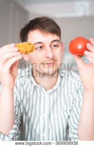 Man Chooses Between Unhealthy And Healthy Food. The Guy Holds The Tomato And Crispy Chicken And Choo