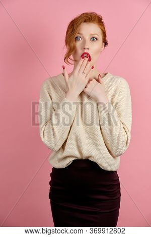 A Red-haired Girl With Red Lips, Stands On A Pink Background, Covers Surprisingly Open Mouth With A
