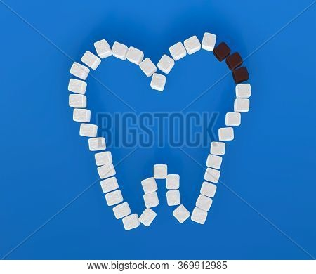 Tooth From Sugar Cubes On Blue Background, Some Brown Sugar Cubes, Concept For Sweet Tooth, Caries.