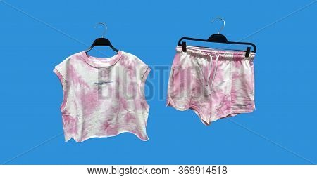 Tie-dye Cropped T-shirt And Jogging Shorts With A Tie-dye Print On A Hanger Isolated. Trendy Clothes