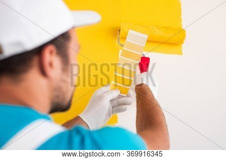 Back View Of Crop Professional Male Decorator Holding Palette Sample And Painting Wall In Bright Yel