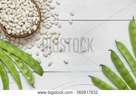 Uncooked Dried White Haricot Beans In Wooden Spoon With Fresh Raw Green Beans Pod Plant On Rustic Ta