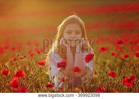 Little Girl In Popply Field At Sunset Time