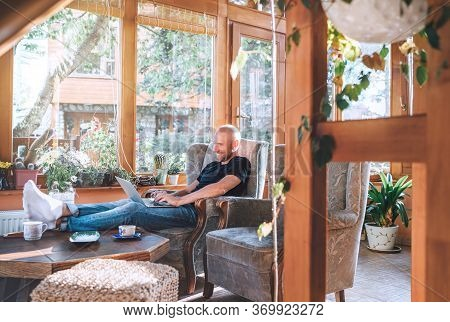 Man Dressed Black T-shirt And Jeans Sitting In A Comfortable Armchair, Using A Modern Slim Laptop An