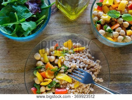 A Meal Served Consisting Of Farro, Garbanzo Bean Salad And Mixed Greens Served With Olive Oil On Woo
