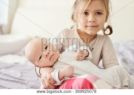 Cute Little Girl And New Born Baby Boy   In A Home Bedroom.