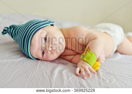 Baby On The Bed With Toy On Wrist