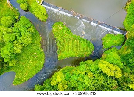 Green heart shaped island on river in Upper Berounka natural park. Wonder of nature near Pilsen. Amazing destination in Czech Republic. Aerial view to European landmark.
