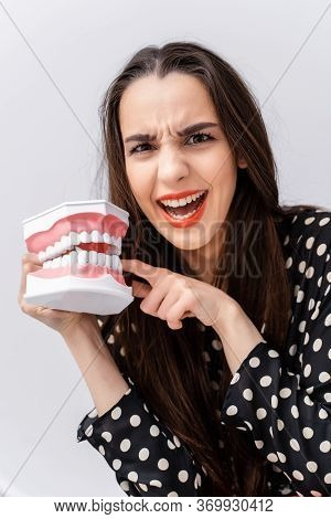 Girl Put Finger To A Dental Educational Jaw. Plastic Jaw Bites A Girl By A Finger. Funny Emotions.