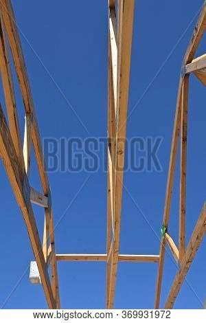 Pre-built Rafters Are Outlined Against The Blue Sky