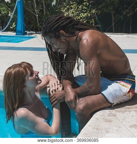 Interracial Couple In The Pool Hugging And Looking At Each Other