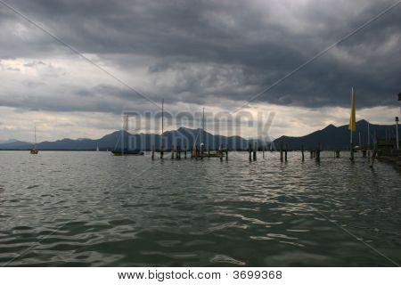 Dark Regenwolken und dem Chiemsee (Deutschland) mit der Bayerischen Alpen.