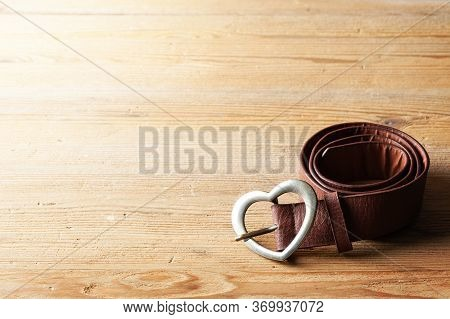 Brown Leather Woman Belt With Metal Heart Shaped Belt Buckle On Wooden Board