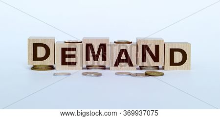 Demand Word Written On Wooden Blocks On Stacks Of Coins With White Backround