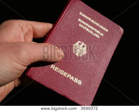 Showing the German Passport in front of black background poster