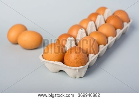 Raw Chicken Eggs In A Egg Box And Two Eggs Next To It On A Grey Background