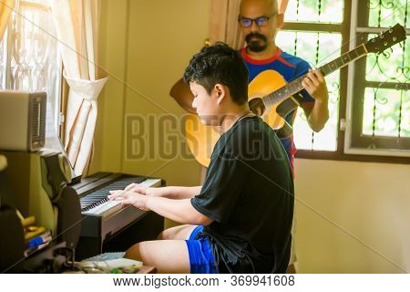 Selective Focus To Asian Boy Is Playing Piano With Blurry Father Playing Guitar In Home. Musical Ins
