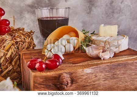 Mozzarella Baby Brie Cheese And Mozzarella Mural With Garlic And Grapes And A Glass Of Wine On A Woo