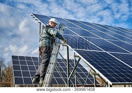 Technician On A Ladder Installing Photovoltaic Solar Batteries On Sunny Day Against Blue Cloudy Sky.