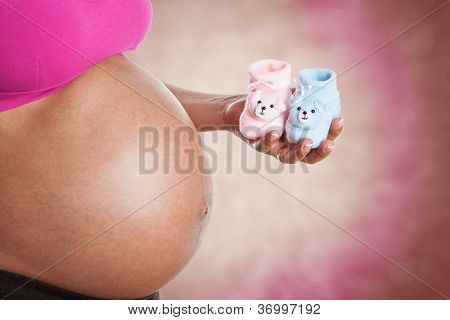 Woman Holding Two Small Baby Booties, Wondering If It Is A Boy Or A Girl