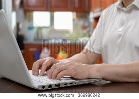 A Middle-aged Man Who Is Dressed Casually At Home And Works From Home Using A Computer. Internet Net