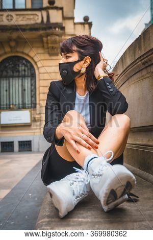 Streetstyle, A Young Brunette With A Face Mask From The Coronavirus Pandemic, Sitting In The City. L