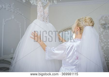 Attractive Bride In White Dress, Touches The Wedding Dress On The Mannequin In Wedding Morning. Tren
