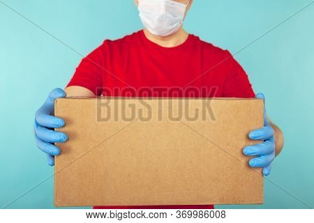 Delivery Package Concept. Courier In Red T-shurt Holding Box Isolated Over The Blue Background.