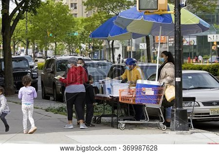 Bronx, New York/usa - May 27, 2020: Food Vendor Outdoors Selling Food As People Wear Masks During Co