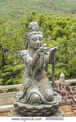 Buddhist Deva Statue Offering Fruit To The Tian Tan Big Buddha  Statue On Lantau Island, Hong Kong